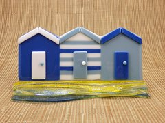 Beach huts in blue and white glass in a sandy yellow and blue wave glass stand