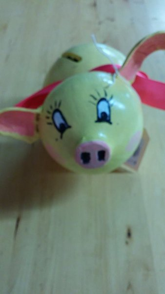 Yellow piggy bank with pink ribbon