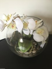 STUNNING TABLE CENTREPIECE IVORY ORCHID WITH LEAVES IN 12 INCH GLASS FISH BOWL. WITH FAUX WATER & POLISHED COBBLESTONES