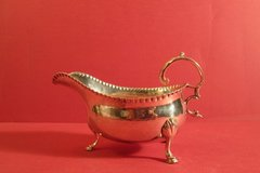 Sterling silver sauceboat with repoussé gadrooned border, on paw feet with Chippendale handle. London, 1778 by James Stamp.